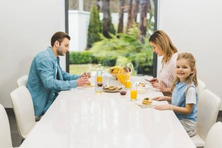 Photo for Side view of parents and little daughter having breakfast together at home - Royalty Free Image