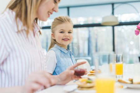 side view of mother and daughter having breakfast together at home