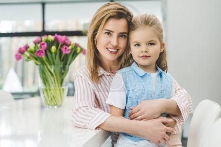 portrait of smiling mother hugging little daughter at home