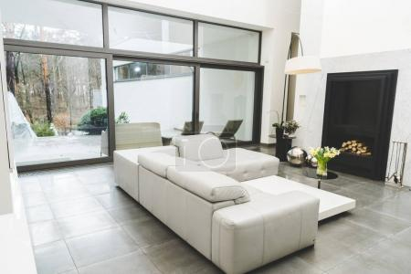 view of empty living room with white sofa and bouquet of flowers on coffee table