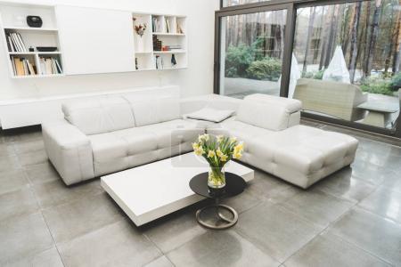 Foto de Vista de la vacía sala de estar con sofá blanco y ramo de flores sobre mesa de centro - Imagen libre de derechos