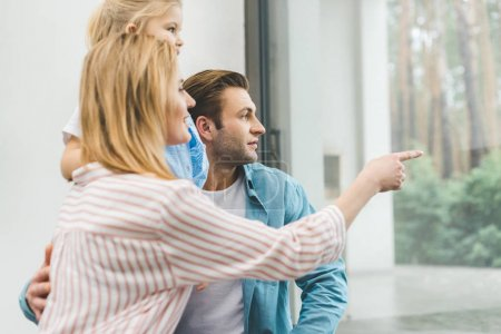 Photo for Side view of family looking out window together at home - Royalty Free Image