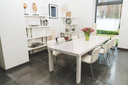 Photo pour Vue de l'élégante salle à manger vide avec bouquet de tulipes sur table - image libre de droit