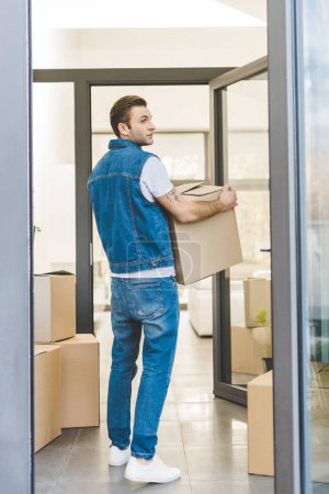 Photo for Back view of man with cardboard box moving new house - Royalty Free Image