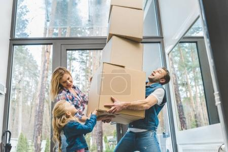 happy family holding cardboard boxes together at new home, moving home concept