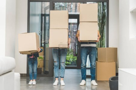 partial view of family holding cardboard boxes at new home, moving home concept