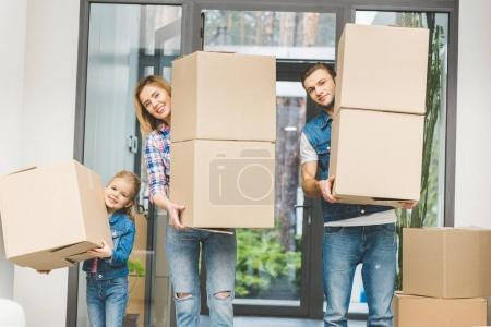 Photo for Family holding cardboard boxes at new home, moving home concept - Royalty Free Image