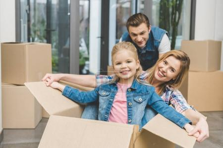 Photo for Portrait of smiling parents and little daughter in cardboard box at new home, moving home concept - Royalty Free Image