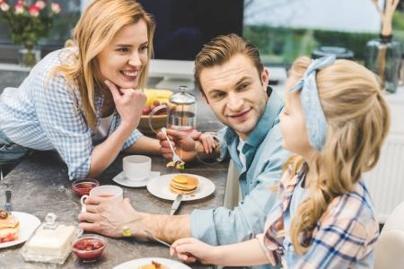 parents and little daughter having breakfast together at home