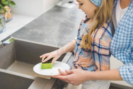 Photo pour Plan recadré de petite fille aidant la mère à laver la vaisselle après le dîner dans la cuisine - image libre de droit