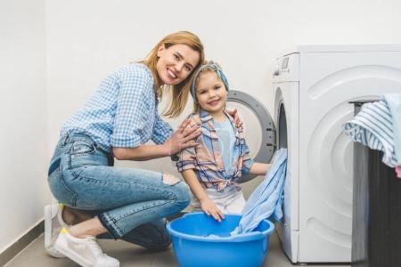 mother and daughter looking at camera while putting clothes into washing machine at home