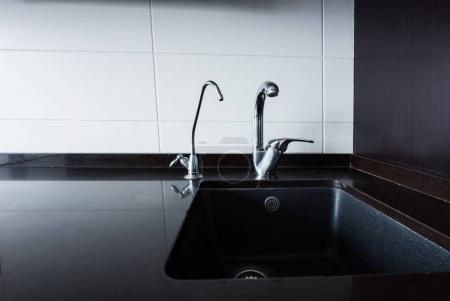 close up view of sink and faucets in kitchen