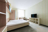 close up view of stylish bedroom with wooden closet and bed