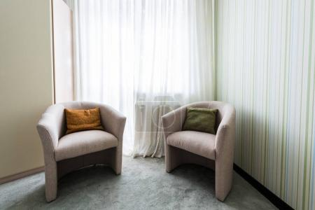 close up view of armchairs at window in room