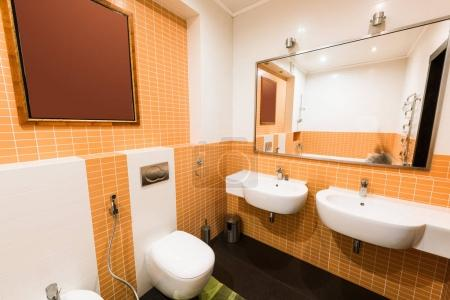 close up view of modern bathroom in orange and white colors
