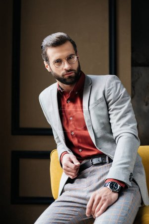 Photo for Handsome bearded man in glasses and stylish suit sitting on couch - Royalty Free Image