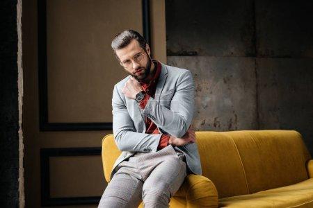 Photo pour Bel homme élégant en lunettes et costume assis sur le canapé - image libre de droit