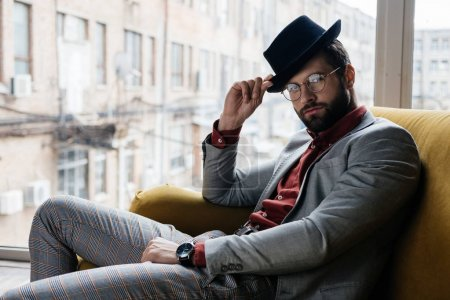 Photo for Handsome stylish elegant man in eyeglasses and hat sitting on couch - Royalty Free Image