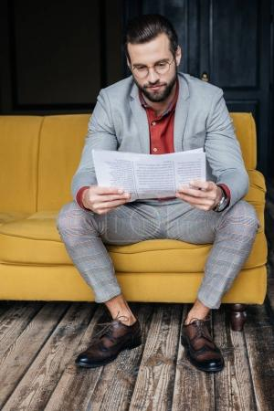 Photo for Stylish man in trendy grey suit reading newspaper and sitting on couch - Royalty Free Image
