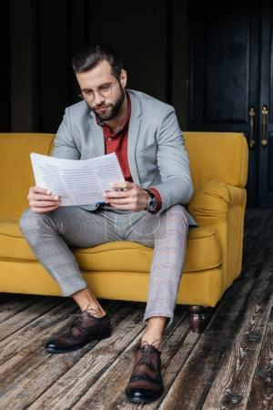 handsome stylish man in trendy suit reading newspaper and sitting on couch