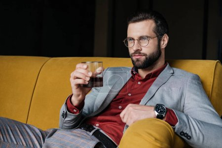 stylish handsome man holding glass of whiskey