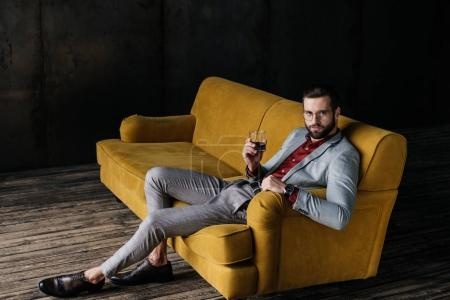 stylish handsome man holding glass of cognac and sitting on yellow couch