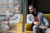 Handsome bearded man sitting on yellow couch at window with reflection