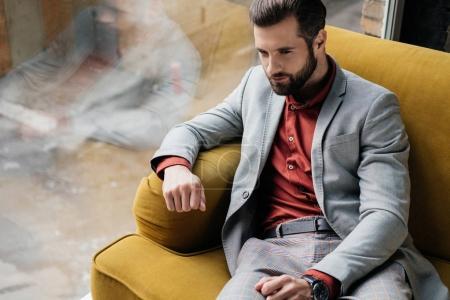 Photo pour Bel homme à la mode assis sur le canapé jaune à la fenêtre - image libre de droit