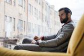 stylish pensive man sitting on yellow sofa at window