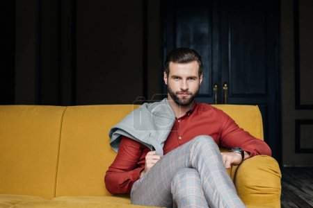 fashionable man sitting on yellow sofa and looking at camera