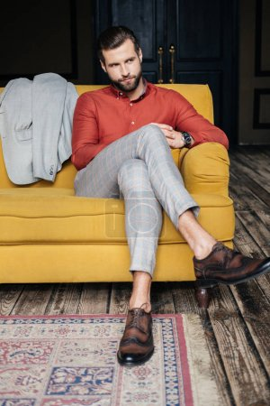 Photo for Elegant man in suit and brogue shoes sitting on yellow sofa - Royalty Free Image