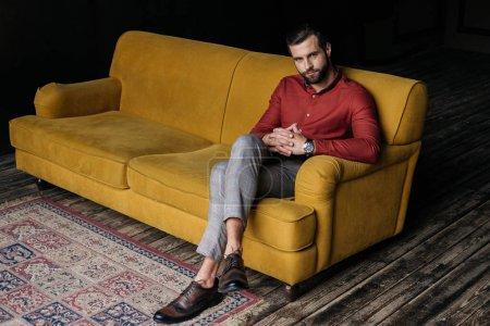 fashionable elegant man sitting on yellow couch