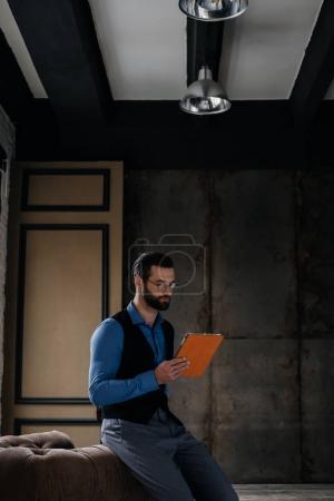 Photo pour La mode homme élégant, à l'aide de tablette numérique en intérieur loft - image libre de droit