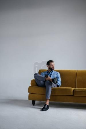 Photo for Elegant man in trendy suit using smartphone and sitting on yellow sofa - Royalty Free Image