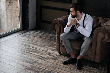 handsome stylish man sitting in armchair and looking at window, loft interior