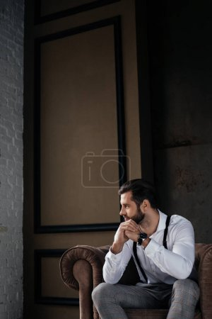 handsome thoughtful man sitting in armchair