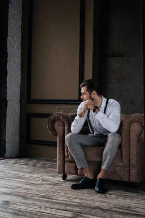 caucasian pensive stylish man sitting in armchair in loft interior