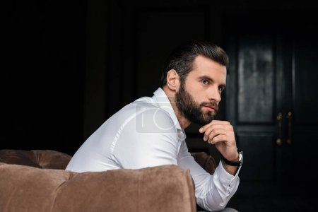 Photo for Thoughtful handsome bearded man sitting in armchair - Royalty Free Image