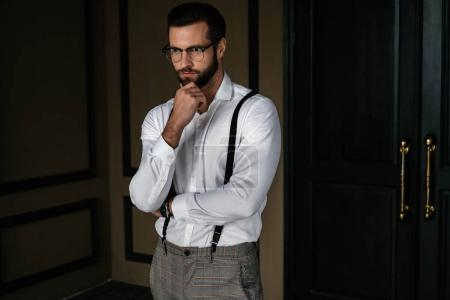 Photo for Handsome bearded pensive man in white shirt and suspenders - Royalty Free Image