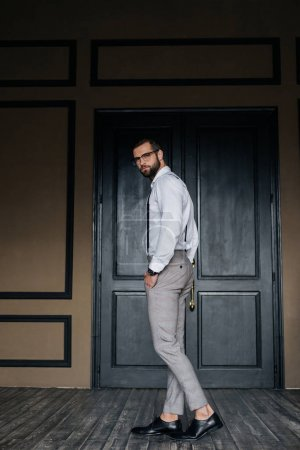 fashionable elegant man posing in white shirt and suspenders against door in loft interior