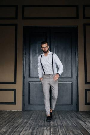 handsome elegant man posing in white shirt and suspenders against door