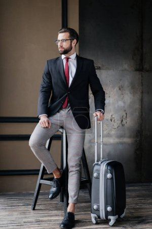 handsome stylish businessman with luggage ready to business trip