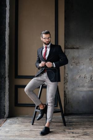 handsome stylish businessman in suit posing on stool in loft interior