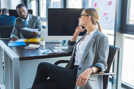 side view of beautiful businesswoman talking by smartphone in office