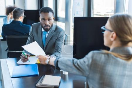 Photo for African american businessman giving documents to businesswoman - Royalty Free Image