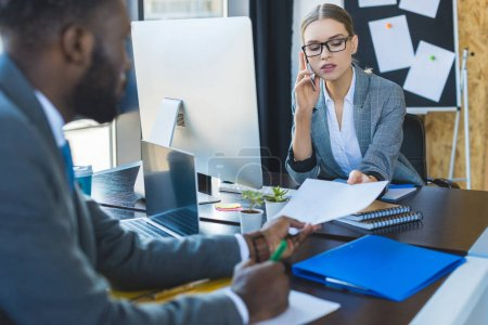 african american businessman giving documents to businesswoman talking by smartphone