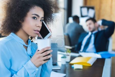 side view of african american businesswoman talking by smartphone in office