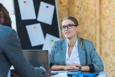 Photo for Smiling multicultural businesswoman and businessman talking in office - Royalty Free Image