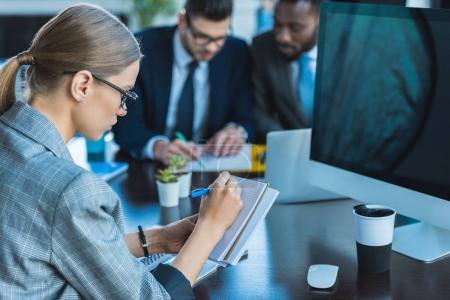 Photo pour Vue latérale d'une femme d'affaires écrire quelque chose pour l'ordinateur portable au bureau - image libre de droit