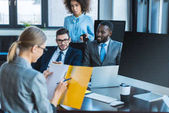 multicultural businesspeople looking at businesswoman with folder in office
